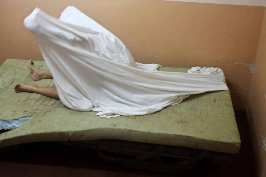 17. Пациентка накрывается простынею с головой в изоляторе психиатрической клиники 14 октября 2009 года. (AP Photo/Esteban Felix)