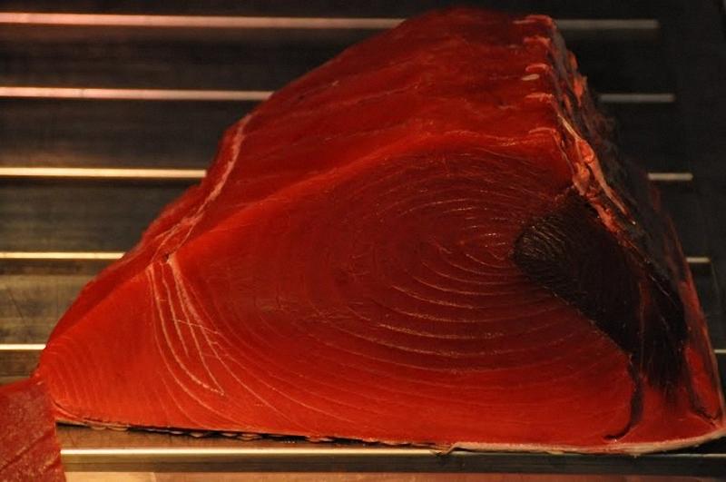 17) Если внимательно присмотреться к этикеткам на коробках с тунцом, которые поступают с утра на рынок Цукидзи, выяснится, что они прибыли чуть ли не со всего света, но преимущественно из Средиземного моря. Это не «дикий», пойманный в открытом море тунец, а рыба со средиземноморских ферм, где тунца разводят специально для японского рынка. Хитрость тут вот в чем. «Дикий» тунец подобен торпеде – он рассекает воду со скоростью до семидесяти километров в час. Мясо его содержит мало жира, ибо в поисках пропитания такой тунец проделывает сотни километров в день. Иное дело привольное житье на рыбоферме, где тунцу обеспечено трехразовое питание; от этого и заводится у него ценимый японскими гурманами жирок. Большинство тунцовых ферм в Средиземноморье, кстати, принадлежит японским владельцам.