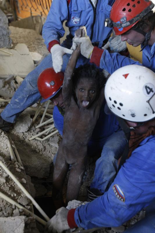 18. Российские спасатели вытаскивают девочку из развалин дома в Порт-о-Пренс 16 января 2010 года, через 4 дня после землетрясения. (UPI/Anatoli Zhdanov)