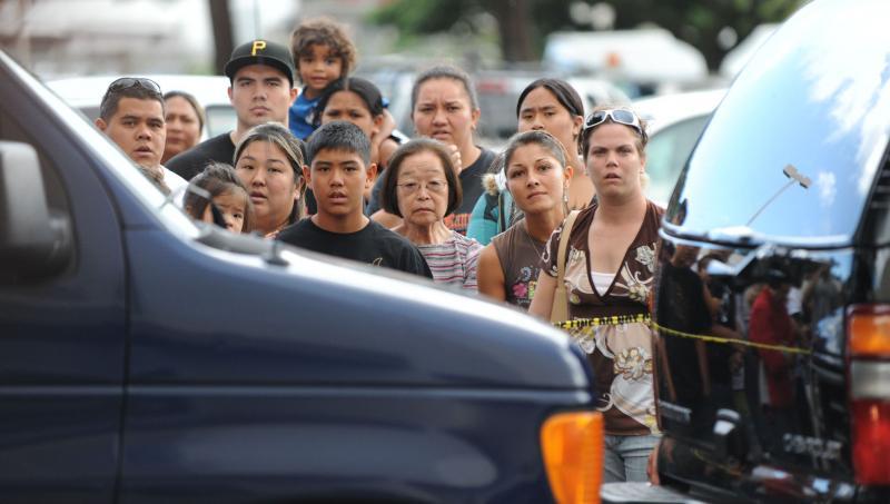 18. Люди смотрят, как президент США Барак Обама и его семья покидают торговый центр «Windward Mall» после просмотра фильма «Аватар» 31 декабря 2009 года. (UPI/Cory Lum/Pool)
