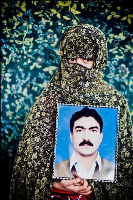 18) Джалиль Раки держит портрет своего пропавшего брата.