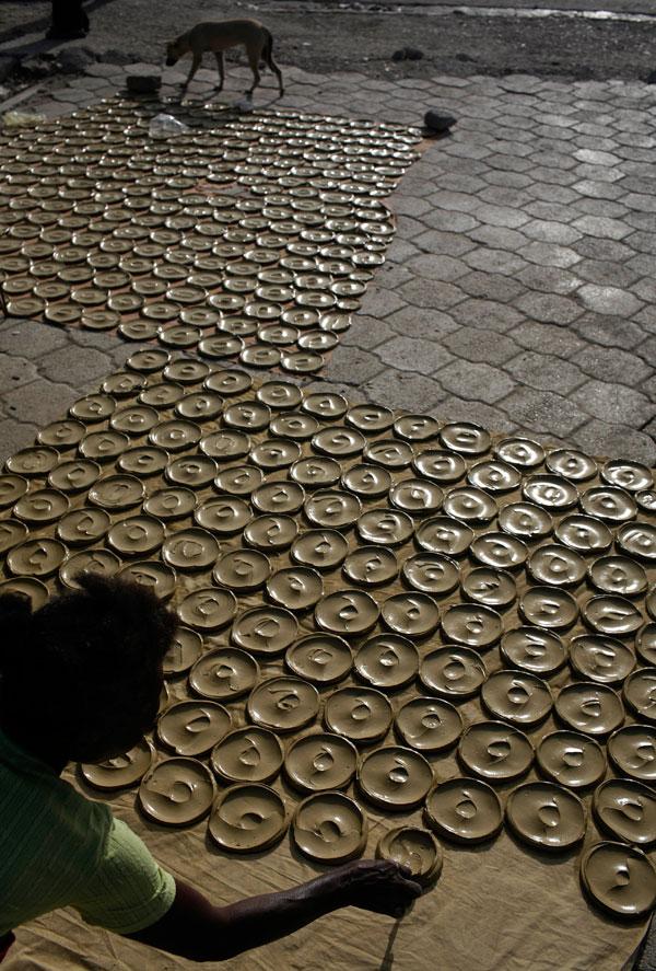 18) Женщина делает печенье из грязи на продажу в районе Сите Солей в Порт-о-Пренс. Печенье готовят из грязи, соли и растительного жира. Это – один из немногочисленных блюд, которые могут позволить себе бедняки на Гаити, после разрушительного землетрясения 12 января. (AP Photo/Rodrigo Abd)