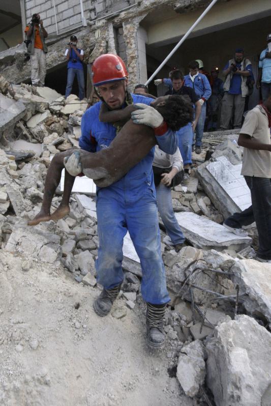 19. Российские спасатели вытаскивают девочку из развалин дома в Порт-о-Пренс 16 января 2010 года, через 4 дня после землетрясения. (UPI/Anatoli Zhdanov)
