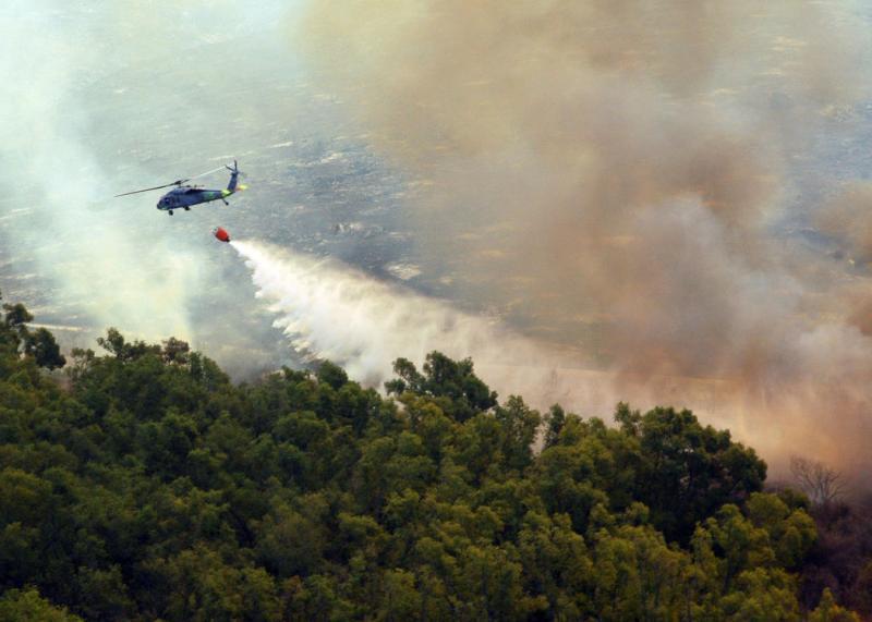 19) Вертолет «MH-60S Seahawk» из 85-ой боевой эскадрильи набирает воду в 1590-литровый ковш, чтобы потушить один из многих районов округе Сан-Диего, пораженных лесными пожарами, 23 октября 2007 года. (UPI Photo/Chris Fahey/USN).