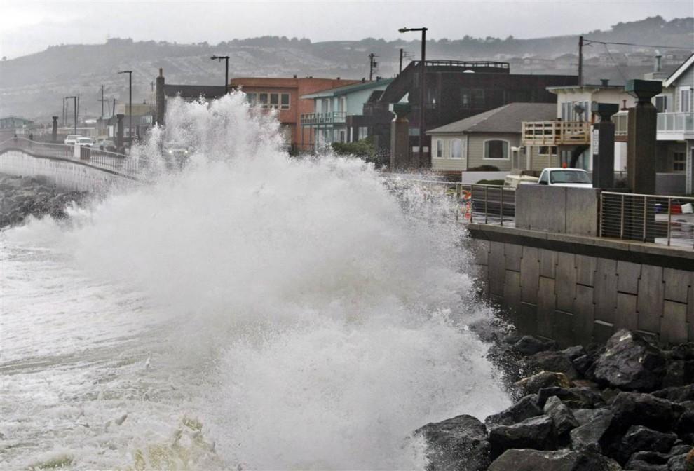 19. Волны бьют о стену пирса недалеко от домов в Пацифике во время ливня. (Paul Sakuma / AP)