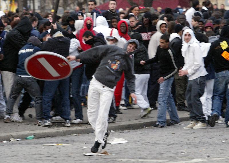 19. Демонстрант бросает знак в отряд полиции, после того как демонстрация против вызвавшего споры контракта по найму молодежи вышла за пределы мирной в Париже 4 апреля 2006 года. (UPI Photo/Eco Clement)