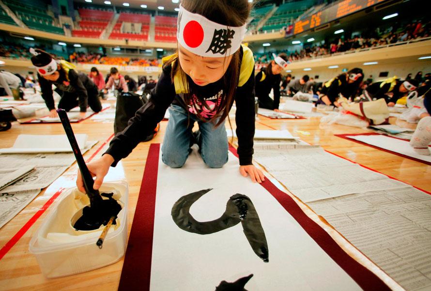 19. Японская девочка рисует новогоднее послание в Будокан Холл в Токио. Около 3500 людей со всей страны приняли участие в ежегодном конкурсе каллиграфии. (AP Photo/Itsuo Inouye)