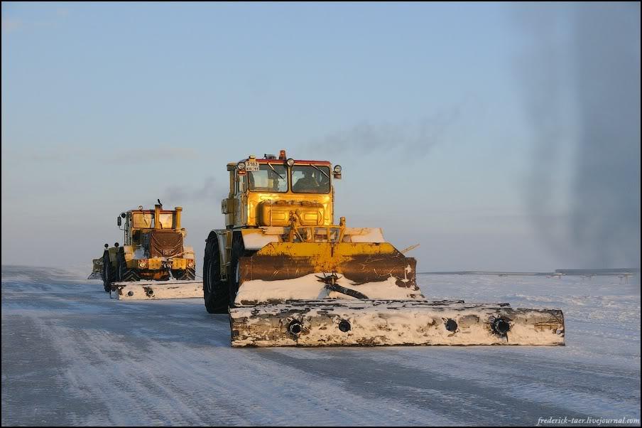 19) Снег топчут тракторами, поливают кипятком и потом ровняют такими чугунными чушками и ставят вешки. Получается настоящая широченная ледяная дорога, хотя и волнистая местами. С каждым снегопадом она становится всё лучше, и отдельные психи прорываются по ней аж до мая (на 6х6 КАМАЗах, конечно).