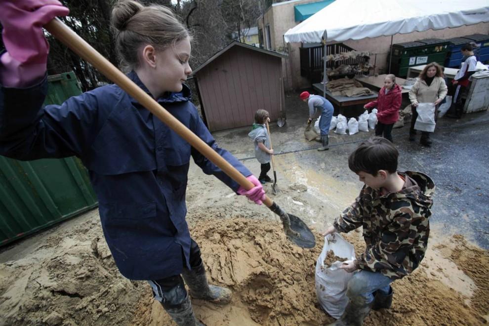 20. 13-летняя Джессика Дженсен (слева) и ее брат 10-летний Дэвид наполняют мешки песком во время своей добровольной работы в Бен Ломонд. (Marcio Jose Sanchez / AP)
