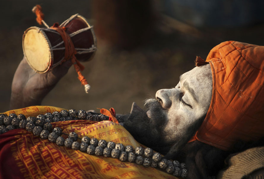 20) Бхолле Натх, индусский садху, ждет милостыни сидя на берегах Сангама, слияния рек Ганги и Ямуны, во время ежегодной ярмарки Магх Мела. (AP Photo/Rajesh Kumar Singh)
