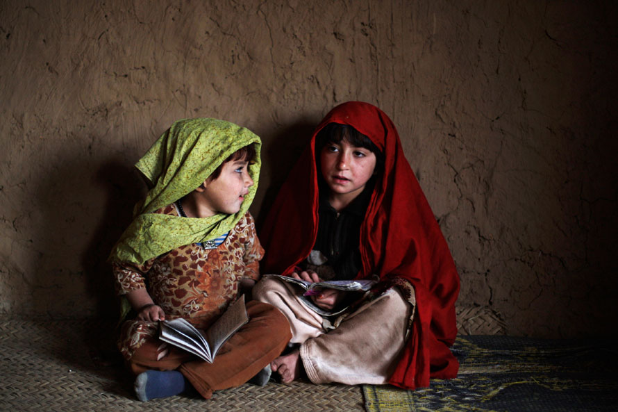 21. Афганские беженки с Коранами пришли на ежедневный урок, чтобы прочитать стихи из Корана в мечети в бедном районе Равалпинди, Пакситан. (AP Photo/Muhammed Muheisen)