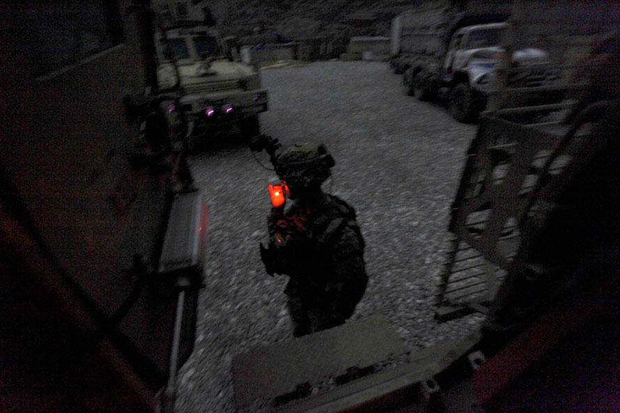 21) В сумерках солдат американской армии курит, прежде чем в его бронированный автомобиль отправится в ночной патруль, на боевом посте Мичиган, в долине Печ, провинция Кунар на северо-востоке Афганистана. (AP Photo/Brennan Linsley)