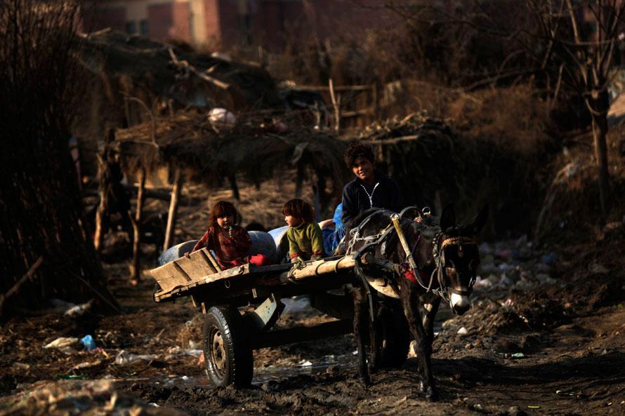 22) Афганский подросток везет маленьких детей на повозке, запряженной осликом в районе на окраине Исламабада. (AP Photo/Muhammed Muheisen)