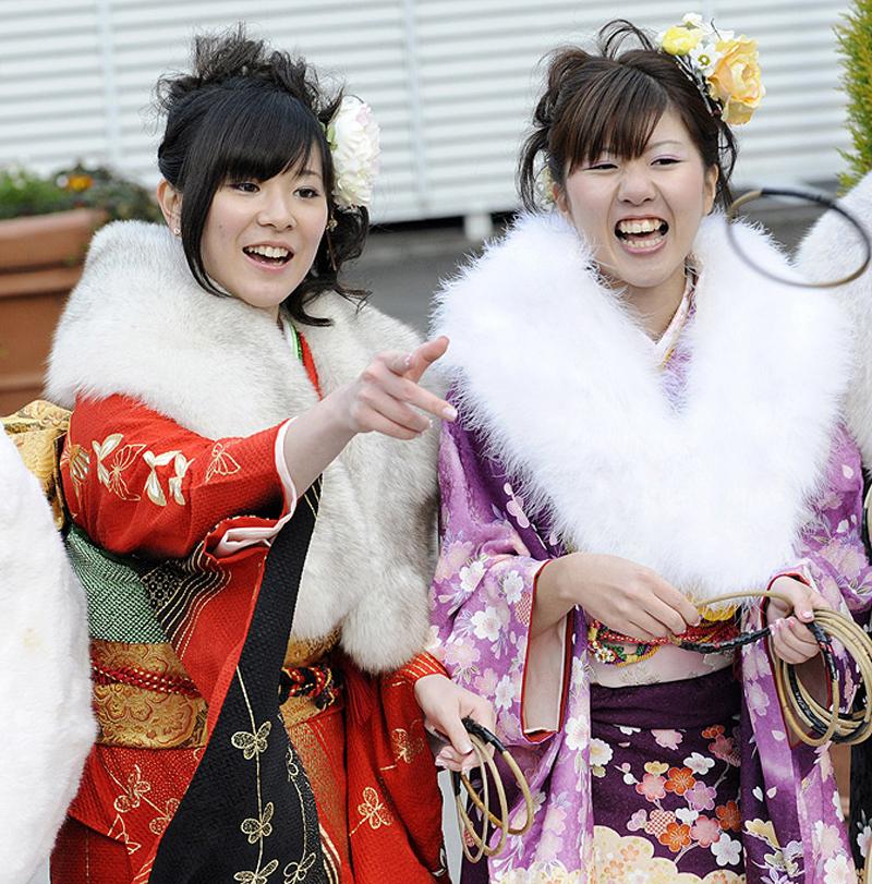 22) Так как праздник проводится в середине января, когда в Токио довольно прохладно, то в последние несколько лет среди девушек стало особо модным надевать на плечи поверх кимоно роскошные меховые манто. (AFP PHOTO/Yoshikazu TSUNO)