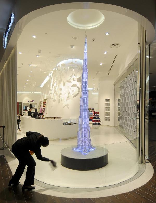 1) Работница сувенирного магазина вытирает витрину, в которой стоит копия знаменитой башни. Магазин находится на входе в центр для посетителей башни.