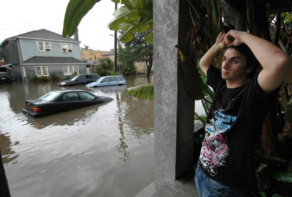 24. Крис Роджерс нашел убежище на крыльце соседнего дома, когда его собственный дом начал заполняться водой после сильного ливня в Лонг Бич. (Scott Smeltzer / AP)
