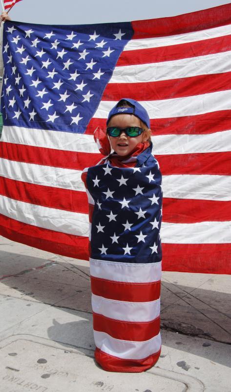 24. Мальчик присоединился к тысячам демонстрантов, прошедшим по улицам Лос-Анджелеса 1 мая 2006 года во время митинга под названием «День без иммигрантов» - протеста сторонником прав иммигрантов против предложенного законодательства в плане реформ закона США касательно иммиграции. (UPI Photo/Jim Ruymen)
