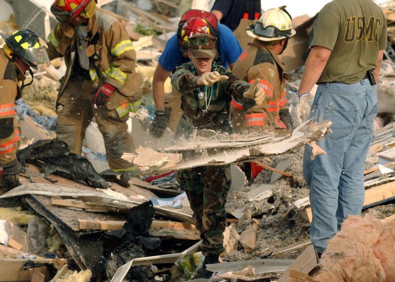 25) Старшина третьего класса Эмми Горман помогает спасателям после того, как торнадо уничтожил стоянку жилых автофургонов в Эвансвилле, штат Индиана, 6 ноября 2005 года. (UPI Photo/ Joseph C. Garza/Navy)