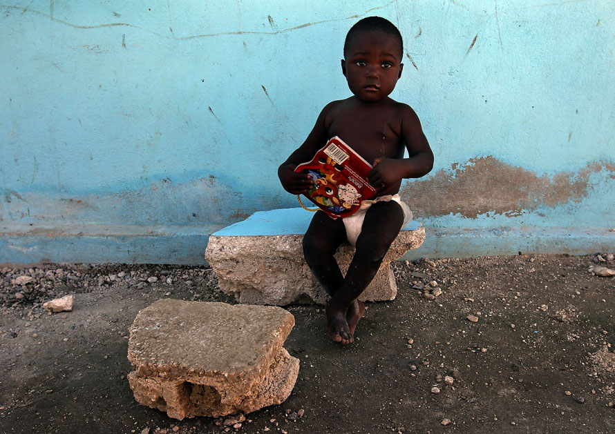 25) Маленький гаитянский мальчик по имени Эдмондсон сидит на разбитом кирпиче у разрушенного здания сиротского приюта в Бон Репо на Гаити. (Photo by Win McNamee/Getty Images)