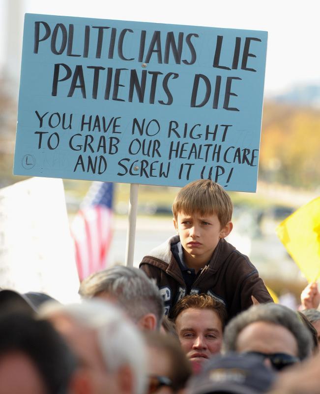 26. Мальчик сидит на плечах мужчина с плакатом во время митинга против реформы системы здравоохранения у Капитолия в Вашингтоне 5 ноября 2009 года. Тысячи демонстрантов пришли на митинг против закона почти в 2000 страниц. (UPI/Roger L. Wollenberg)