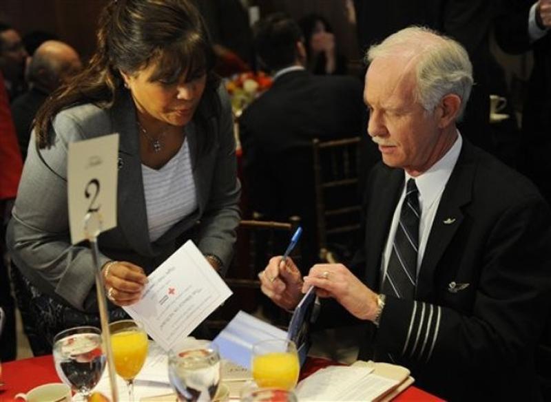 2) Капитан Airways Чесли Селинбергер (Chesley Sullenberger), справа, подписывает свои книги для Джин Диас, волонтера из Красного Креста. (AP Photo/Stephen Chernin)