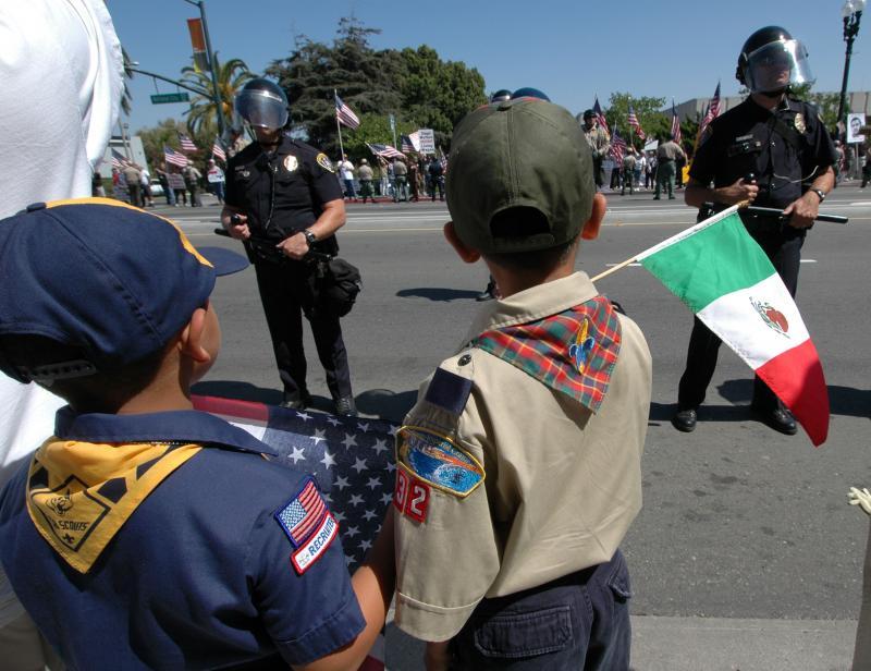 28. Два юных скаута с флагами Мексики и США смотрят через полицейское оцепление, отделяющее их от Сан-Диего Минутемен, протестующих против Нэшнл Сити, Калифорния, и его мэра Ника Инзунза 23 сентября 2006 года. Инзунза хочет, чтобы Нэшнл Сити на севере от мексиканской границы стал прибежищем нелегальных иммигрантов. (UPI Photo/Earl S. Cryer)