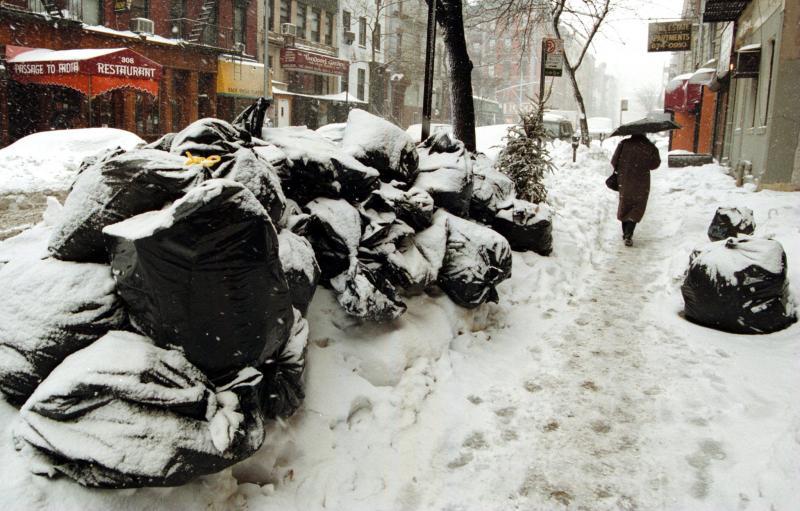 30) Горы мусора лежат вдоль улицы Манхэттена 12 января 1996 года. Мусороуборочные машины не смогли выехать на работу из-за сильной метели. (UPI file photo)