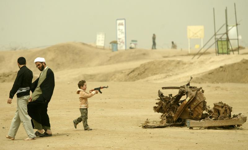 31. Иранский мальчик играет с детским автоматом рядом с проходящими мимо гражданами на месте памятника Ирано-Иракской войне (1980-1988) в 1495 км у юго-западу от Тегерана в провинции Хузестан 24 марта 2007 года. (UPI Photo)