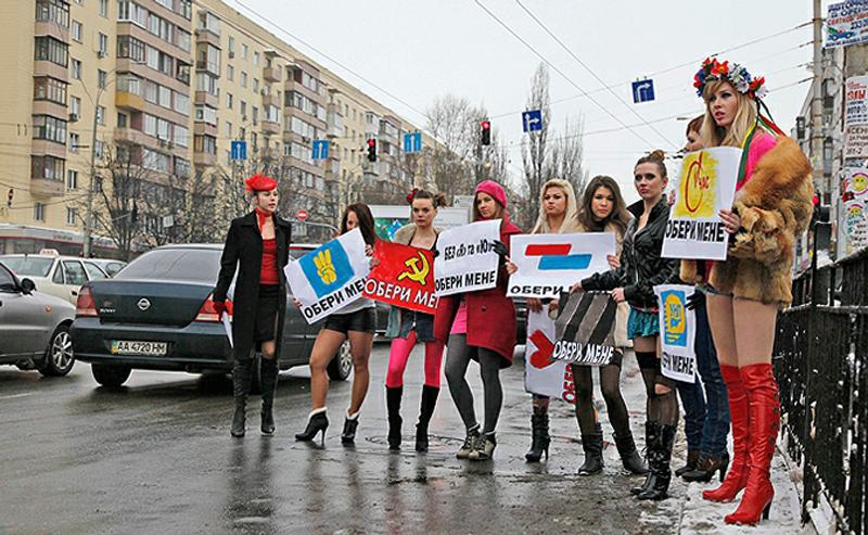 1) Активистки женского движения FEMEN оделись в вызывающе короткие юбки и с агитационными плакатами кандидатов в президенты в руках. (AP)
