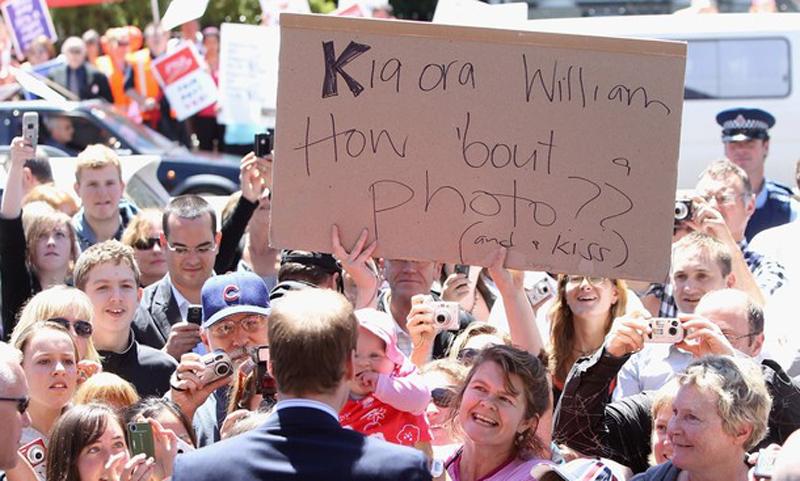 19) Многие жители Новой Зеландии желают сфотографировать принца. Для того чтобы фотография получилаь четкой люди держат плакат с просьбой к Уильяму улыбнуться им. (Chris Jackson/Getty Images)