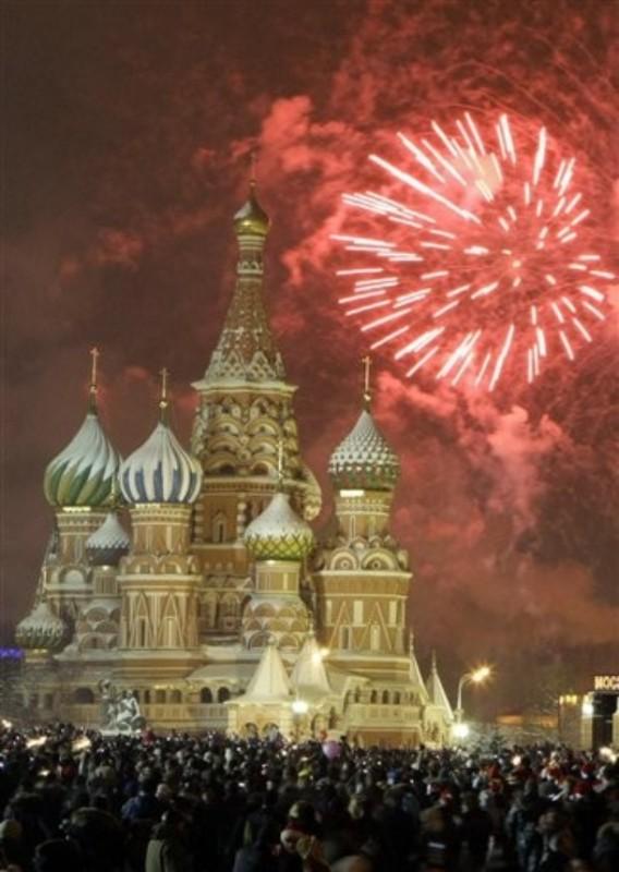 15) Новый год на Красной площади в Москве рядом с собором Василия Блаженного. Десятки тысяч людей вышли на площадь, чтобы отпраздновать Новый год, а также посмотреть фейерверк у часов на Спасской башне Кремля. (AP Photo/Mikhail Metzel)