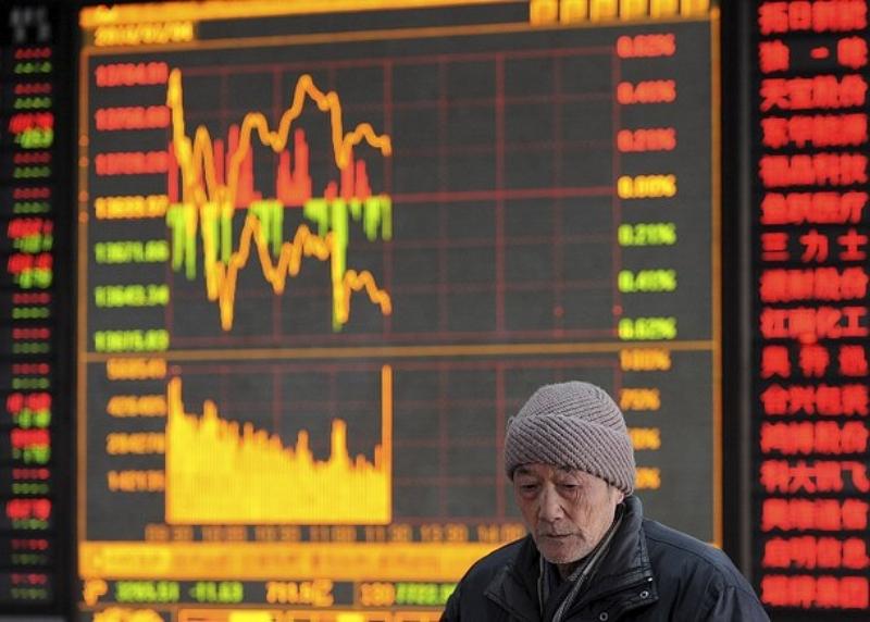 3) Мужчина стоит на фоне электронного табло в брокерской фирме в Хейфей, китайская провинция Анхой. Выбивается из общей динамики лишь континентальный Китай, где зафиксировано падение котировок.