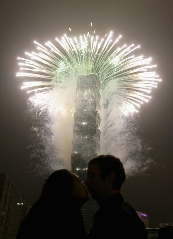 6) Пара целуется у высочайшего небоскреба мира Тайбэй 101 (Taipei 101) во время новогодних праздников в Тайбэй. (REUTERS/Pichi Chuang)