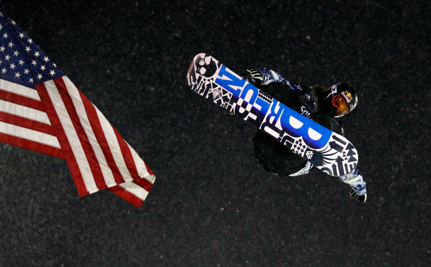 1. Шон Уайт пролетает мимо американского флага в финале Гран-при США по сноубордингу в субботу в Парк Сити, штат Юта. (AP Photo/Colin E Braley)