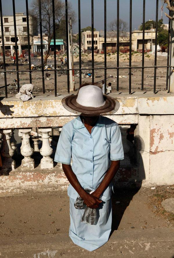 2. Женщина стоит на коленях во время молитвы на воскресной службе, которую проводили на руинах Национального собора, уничтоженного землетрясением 12 января, в Порт-о-Пренс. (AP Photo/Gerald Herbert)