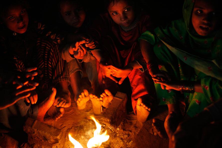 9) Пакистанцы собрались вокруг костра, чтобы согреться в своем временном пристанище в Лахоре. (AP Photo/Muhammed Muheisen)