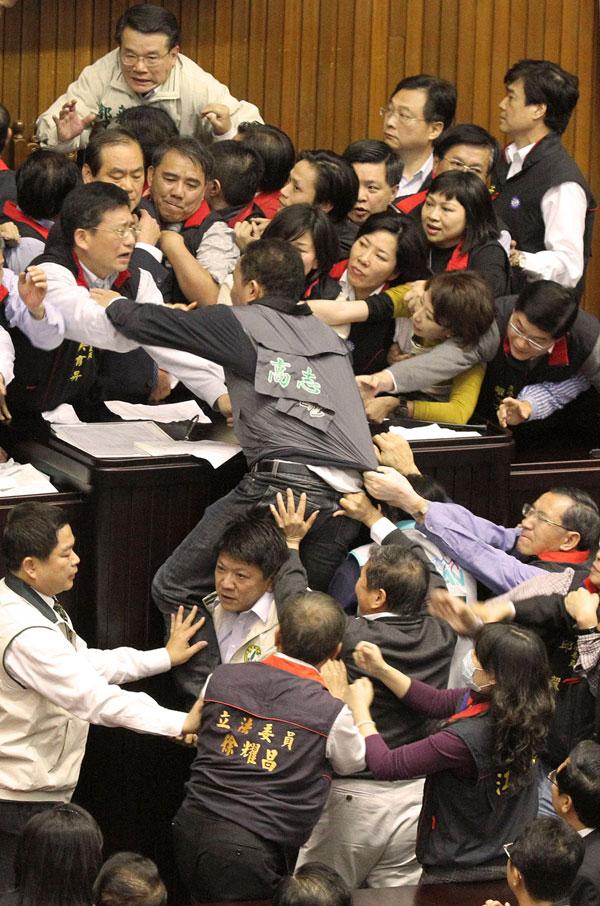 3. Законодатели правящей Националистической партии и оппозиционной Демократической прогрессивной партии дерутся во время заседания в Тайбэе, Тайвань. Чиновники сцепились во время обсуждения поправки к местному государственному закону, после того как две стороны не смогли прийти к соглашению. (AP Photo)
