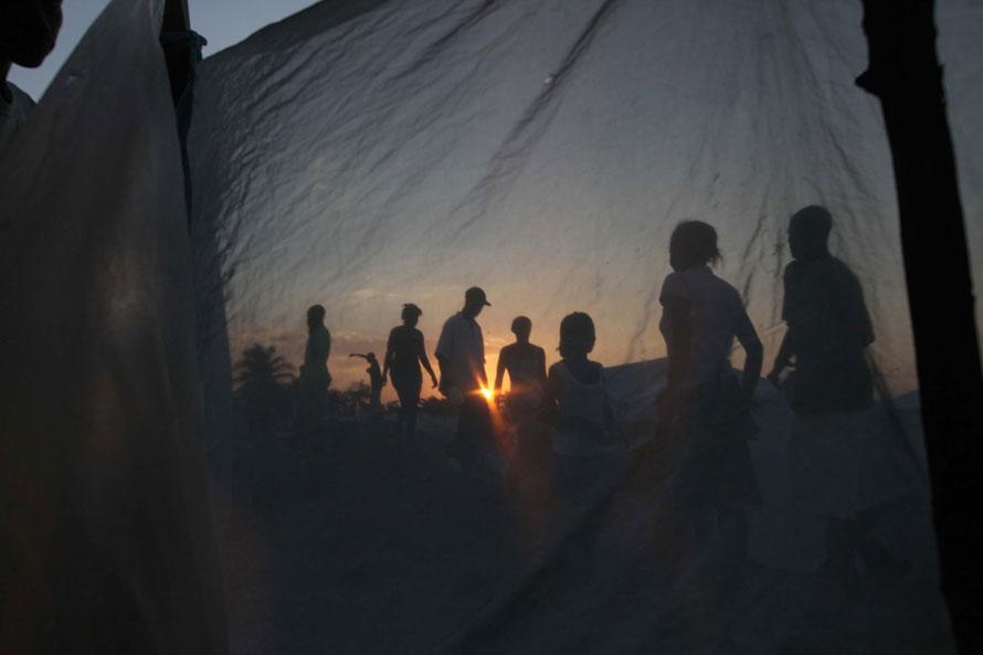 3. Люди идут к своим палаткам в полевом лагере, возведенном на обломках разрушенных домов в Порт-о-Пренс. Правительство Гаити сделало заявление, что около 400 000 человек, оставшихся без крова из-за землетрясения, будут перемещены из своих лагерей в специальные районы за пределами города. (Photo by Joe Raedle/Getty Images)