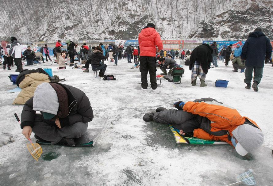 8. Южнокорейские рыбаки смотрят в проруби во время соревнования по ловле форели в уезде Хвачхон. Соревнование является частью ежегодного фестиваля льда, который привлекает каждый год около 1 000 000 посетителей. (AP Photo/Ahn Young-joon)