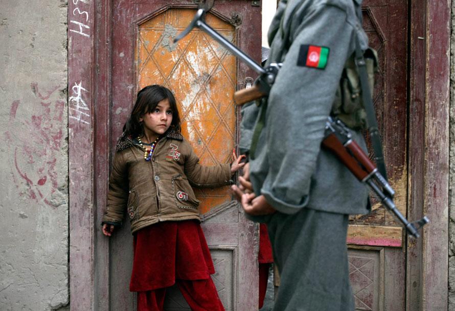 8. Афганская девочка смотрит с порога своего дома на солдата Афганской национальной армии, обыскивающего территорию, которая недавно использовалась боевиками «Талибана»в качестве оборонительной позиции. Снимок сделан во время патрулирования долины Пех, провинция Кунар. (AP Photo/Brennan Linsley)