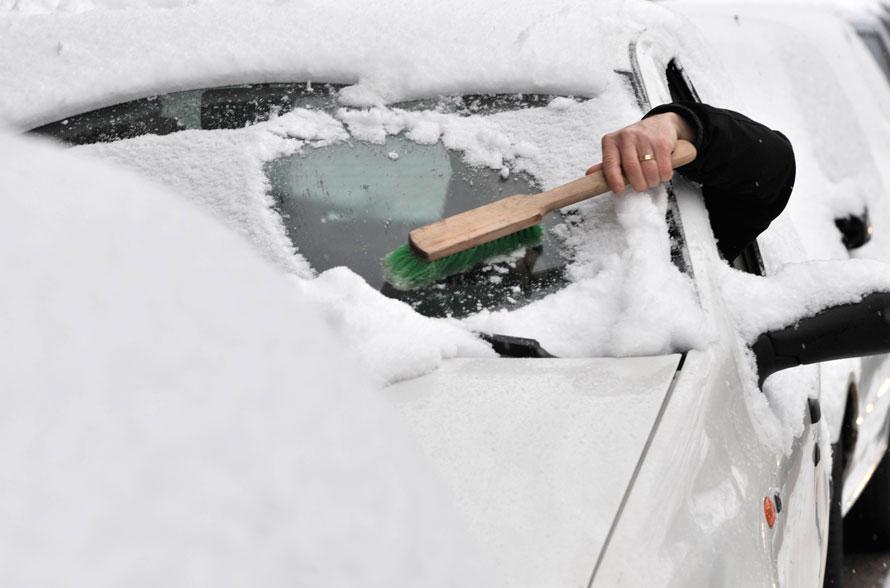 9. Водитель чистит лобовое стекло во время снегопада в Будапеште. Обильные снегопады в Венгрии утром вызвали проблемы на дорогах по всей стране. (AP Photo/Bela Szandelszky)