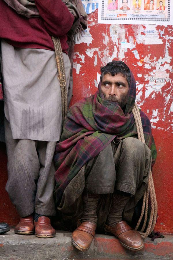 5) Рабочие в шерстяных платках пытаются укрыться от дождя в холодное и туманное утро в индийском городе Джамму. В эти выходные из-за густого зимнего тумана были отменены авиа и железнодорожные рейсы в большей части Северной Индии. (AP Photo/Channi Anand)