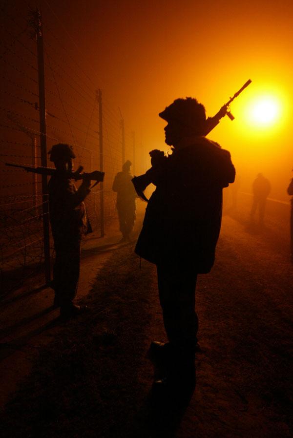 10. Солдаты индийской пограничной службы безопасности патрулируют в густом тумане вдоль ограждения на индийско-пакистанской международной границе в Ранбир Синг Пура, на окраине Джамму. (AP Photo/Channi Anand)
