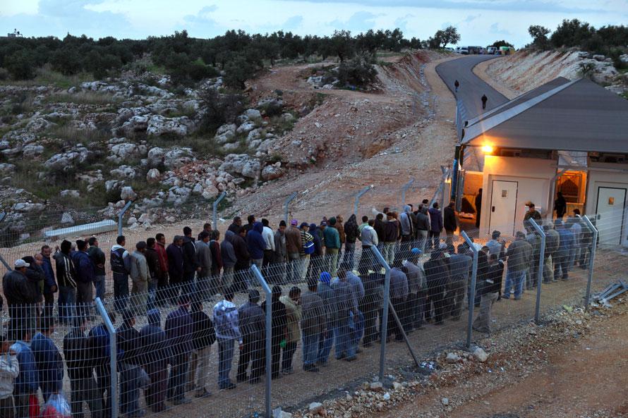 6) Палестинские рабочие стоят в очереди на израильском контрольно-пропускном пункте по возвращении в свои дома после рабочего дня на территории Израиля. Снимок сделан в воскресенье неподалеку от деревни Нилин на Западном берегу. (David Silverman/Getty Images)