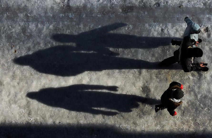 12. Тени прохожих на покрытой льдом улице в баскском городе Витория, северная Испания. Ледяной ветер гуляет по стране, а в некоторых частях Испании продолжаются морозы и снежные бури. (AP Photo/Alvaro Barrientos)
