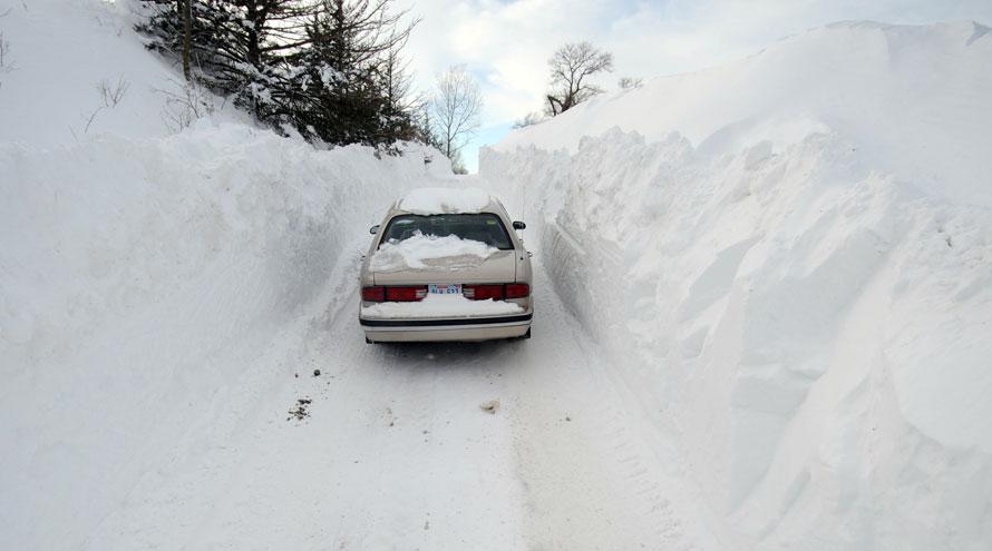 13. Водитель пытается проехать по сельской дороге недалеко от Элкхорна, штат Небраска. Недавние снегопады и ветер создали большие наносы, создавая проблемы для водителей по всей Небраске. (AP Photo/Dave Weaver)