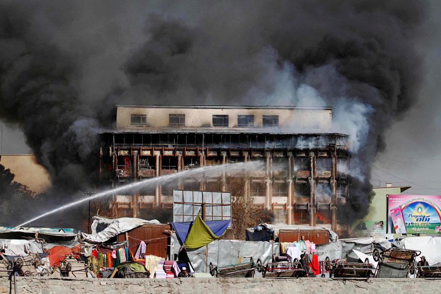 13. Торговый центр горит в центре Кабула. Боевики организации «Талибан» совершили теракт прямо в сердце Афганистана, устроив перестрелку после того, как террорист-смертник взорвал себя рядом с президентским дворцом. Афганскую столицу потрясли новые взрывы, когда войска начали перестрелку с боевиками. (AP Photo/Musadeq Sadeq)
