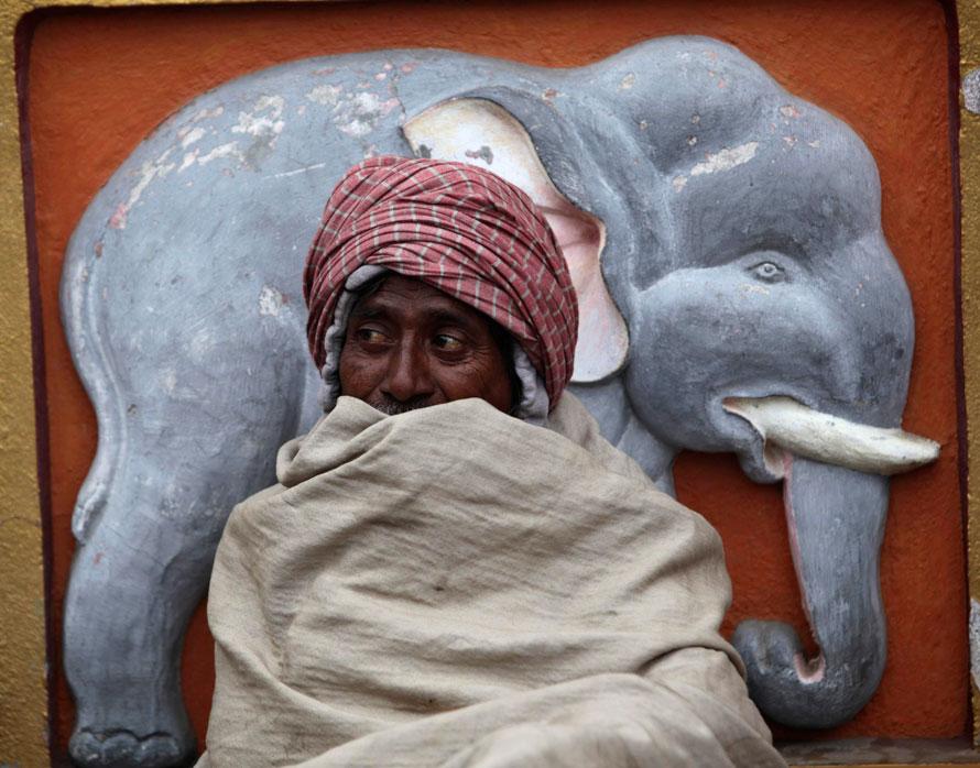 14. Мужчина в одеяле сидит морозным утром у храма Махабодхи в ожидании милостыни в Бодх Гайа, примерно в 130 км к югу от Патны, Индия. В северной Индии продолжаются туманы и морозы. (AP Photo/Rajesh Kumar Singh)