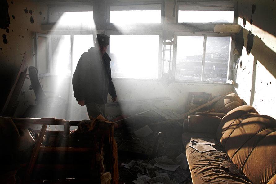 14. Афганский полицейский оценивает ущерб, нанесенный зданию во время перестрелки в Кабуле. (AP Photo/Musadeq Sadeq)