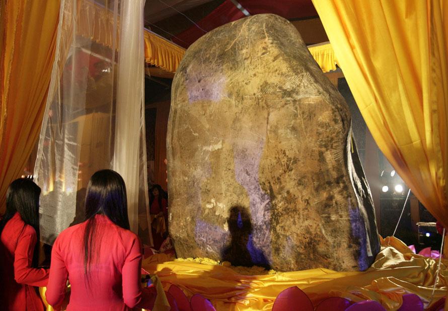16. Девушки смотрят на представленный публике кусок жадеита в провинции Хаи Дуон, Вьетнам. Камень, импортированный из Мьянмы, составляет 298 см в высоту, 213 см в ширину и 219 см в толщину, а весит он 35 тонн. Он считается самым большим в мире куском жадеита. (AP Photo/Tran Van Minh)